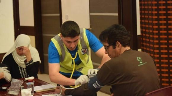 zakat foundation worker taking someone's blood pressure