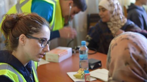 zakat foundation member talking to a refugee