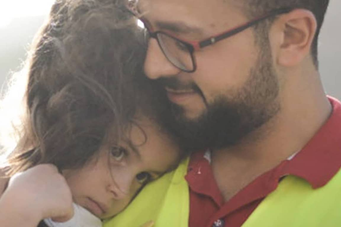 Image of Zakat Foundation worker and refugee female child in arms supported by your giving.