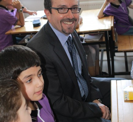 The ambassador in a classroom with kids around him