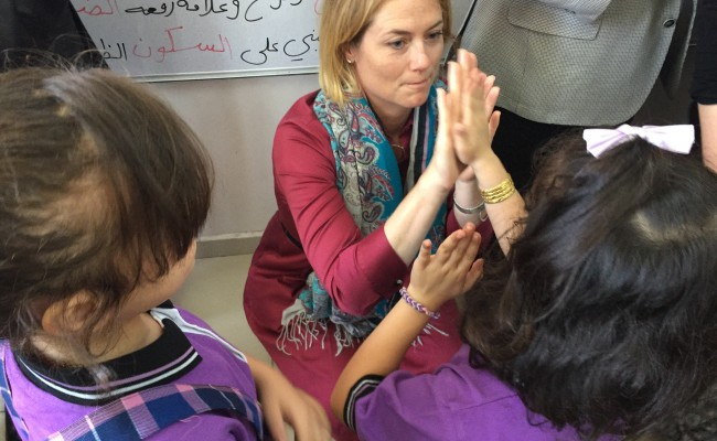g A Syrian refugee student shares a high-five with Mrs. Holzer Bass.
