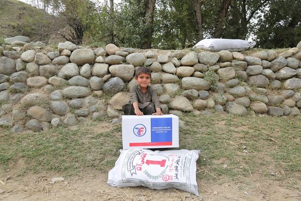 little kid with boxes from the emergency relief