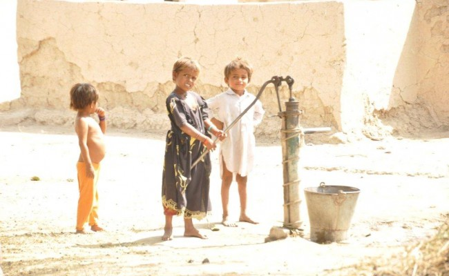 Children in Thar pump water from a well.
