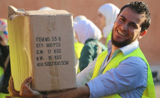 zakat foundation team member with a box of bags