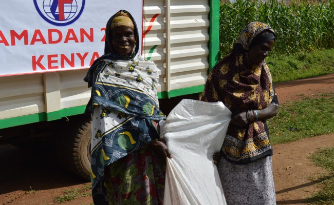 two smiling recipients taking holding their newly arrived supplies