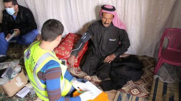 zakat foundation worker taking a refugee's blood pressure