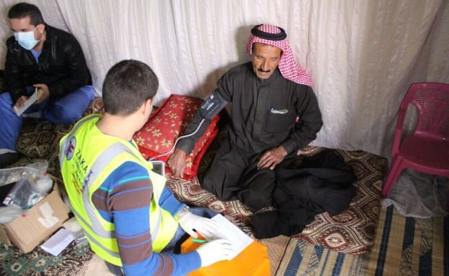 zakat foundation worker taking a refugee's blood pressure
