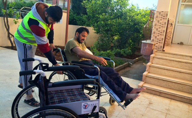zakat foundation member helping one of the receivers to get on their wheelchair
